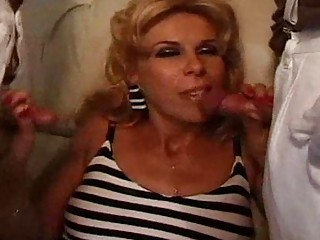 Mature blonde fucks with a bunch of clowns