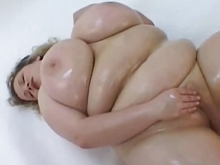 Big breasted oiled MILF masturbates in her